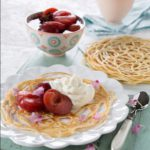Lace pancakes with poached plums and cardamom scented cream