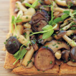 Wild mushroom tart with porcini vinaigrette and pea shoots