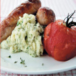 Bangers and herby mash with roasted vine tomatoes