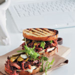 Grilled sandwich of BBQ beef brisket with mayo, gherkins and wild rocket