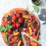 Spelt pizza with heirloom tomatoes, nectarine, prosciutto and kale pesto