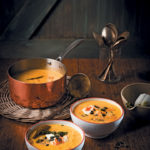 Smoky pumpkin chowder soup with pumpkin seed pesto and sriracha crème