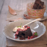 Gooey chocolate cake served with crème fraîche and pomegranates
