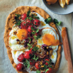 Chickpea flour flatbread topped with garlicky yoghurt, fried eggs, vine tomatoes and olives
