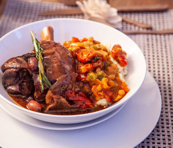Roasted lamb shanks with creamy samp and Durban curry chakalaka